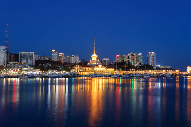 View of the seaport, promenade and panorama of the city. Reflections of night lights in the water in the background of the evening dark blue sky Sochi, Black Sea sochi stock pictures, royalty-free photos & images