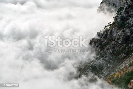 istock View of the slope rocky mountain above fog and clouds 1286907056