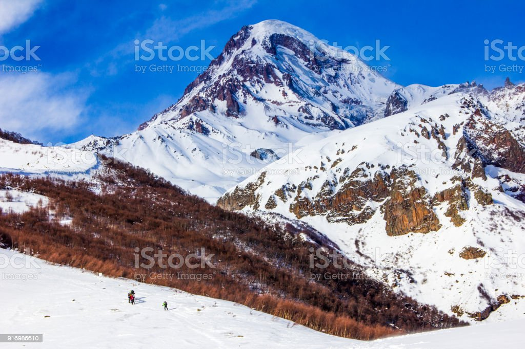 View of the snow-covered Kazbek, a group of skiers rises to the top stock photo