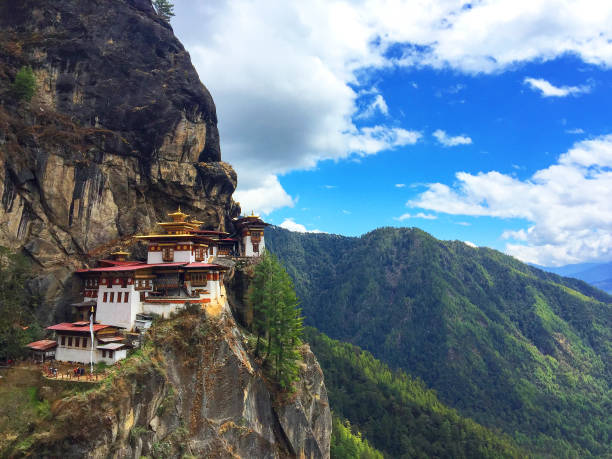 View of the spectacular Tiger's Nest Monastery (Taktsang Palphug Monastery) on a cliff of Paro Valley in Bhutan View of the spectacular Tiger's Nest Monastery (Taktsang Palphug Monastery) on a cliff of the Paro Valley in Bhutan. The Tiger's nest is a prominent and difficult to access Himalayan Buddhist holy site first built in 1692 around the Taktsang Senge Samdup cave where Guru Padmasambhava, who introduced Buddhism to Bhutan, meditated for three years. Paro (Dzongkha) is an ancient town in the homonymous valley, with many sacred sites, temples and historical buildings. Bhutan is famous for pioneering the concept of Gross National Happiness. monastery stock pictures, royalty-free photos & images