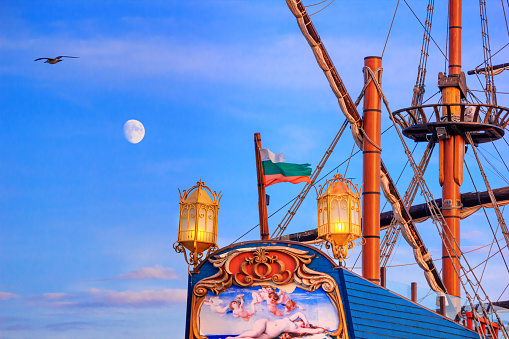 View of the stern of a stylized vintage sailboat against the background of the evening sky in the port of Varna, on the Black Sea coast of Bulgaria, 10 September, 2019