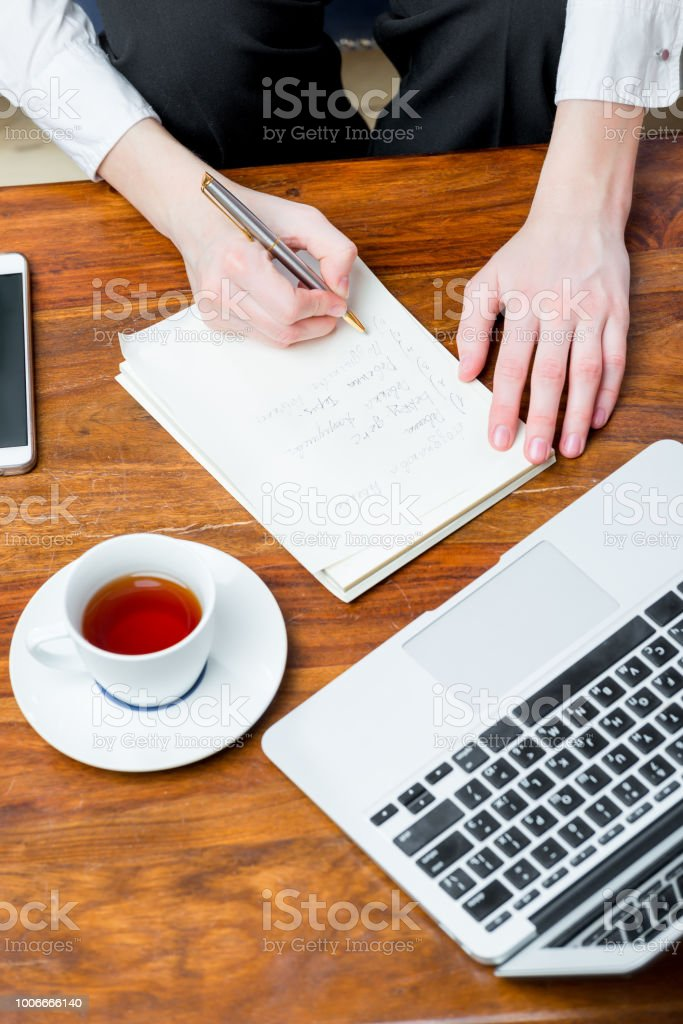 view of the top of the hand at work, writing important information to the notebook stock photo