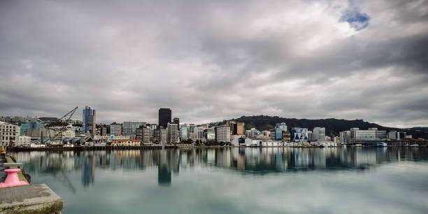 View of the Wellington waterfront on a windy day. Wellington, New Zealand Long exposure of the waterfront beautifully reflected in the harbour wellington new zealand stock pictures, royalty-free photos & images