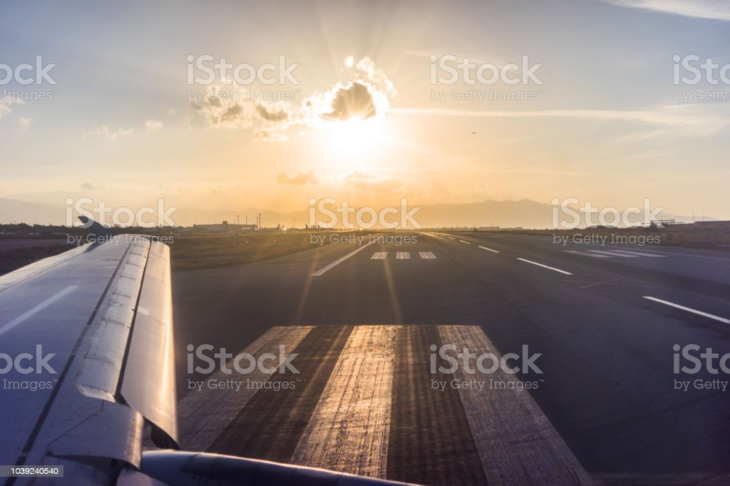 View of the wing of the aircraft from the porthole on the background of the runway stock photo