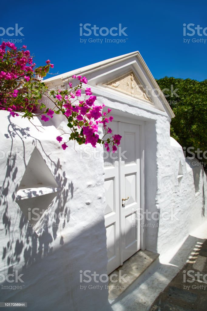 View of traditional neoclassical houses with beautiful bougainvillea flowers in pictruesque streets of Andros island chora, Cyclades, Greece stock photo