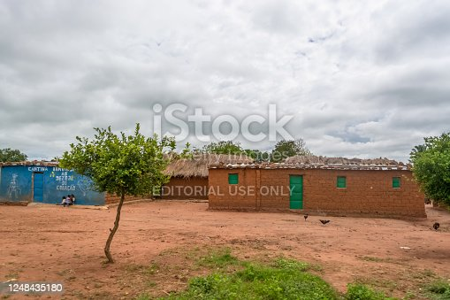 Malange / Angola - 12 08 2018: View of traditional village, kids and chickens outside, thatched and zinc sheet on roof houses and terracotta brick walls, cloudy sky as background, in Angola