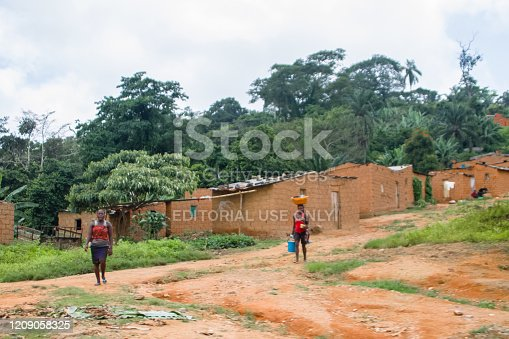 Gabela / Kwanza Sul / Angola - 02 25 2020: View of traditional village, thatched and zinc sheet on roof houses and terracotta brick walls, women carrying things, in Angola