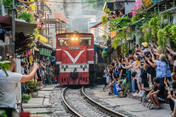 View of train passing through a narrow street of the Hanoi Old Quarter. stock photo