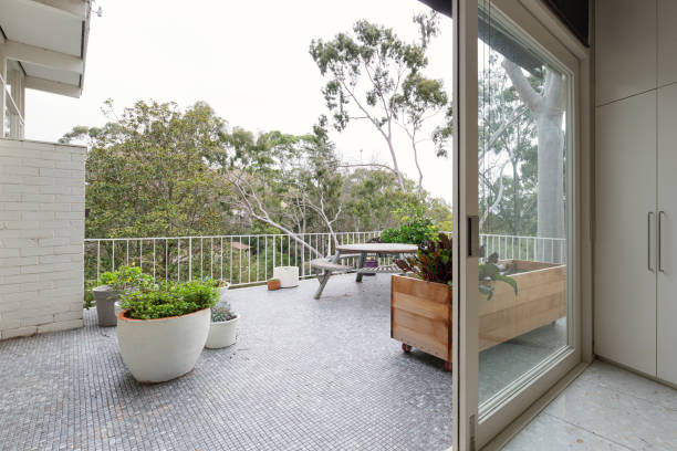 View of treetops from large mosaic tiled terrace in Australian luxury home stock photo