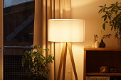 istock View of tripod lamp in a cozy living room spending warm light 1296013606