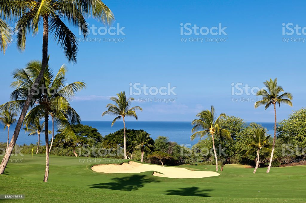 View of tropical golf course by waterfront stock photo