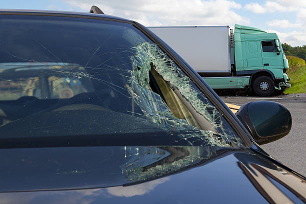 View of truck in an accident with car, broken glass stock photo