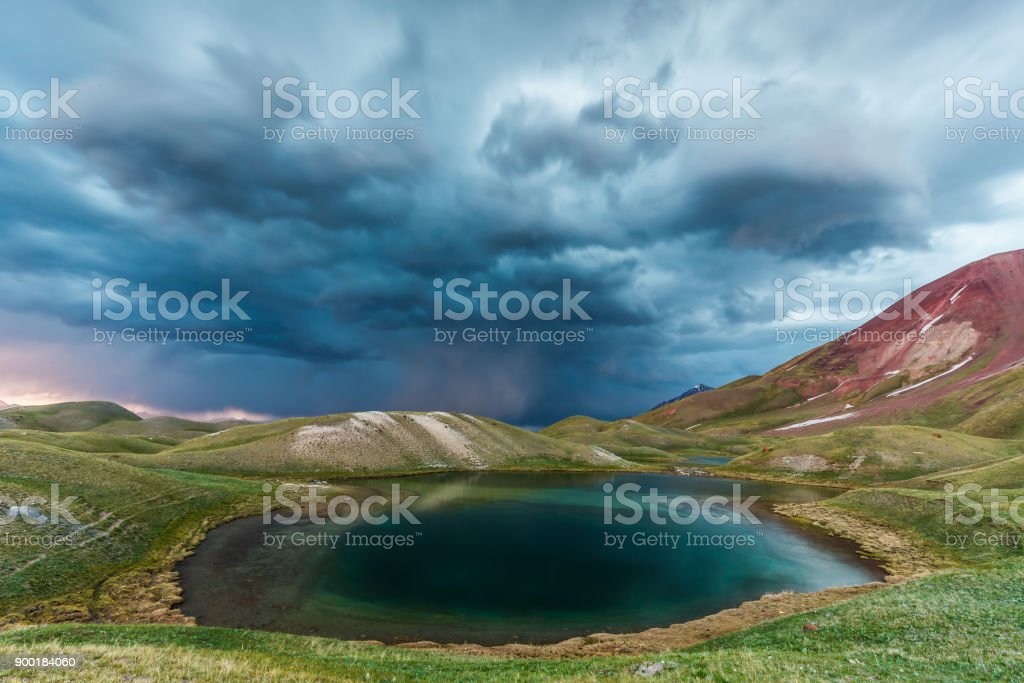 View of Tulpar Kul lake in Kyrgyzstan during the storm stock photo