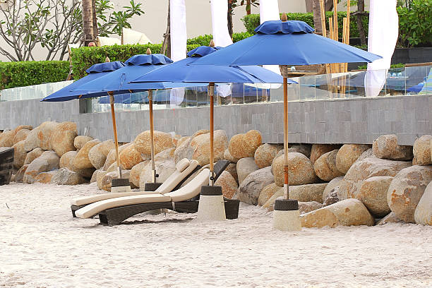 view of two chairs and umbrella on the beach - dawdle stock pictures, royalty-free photos & images