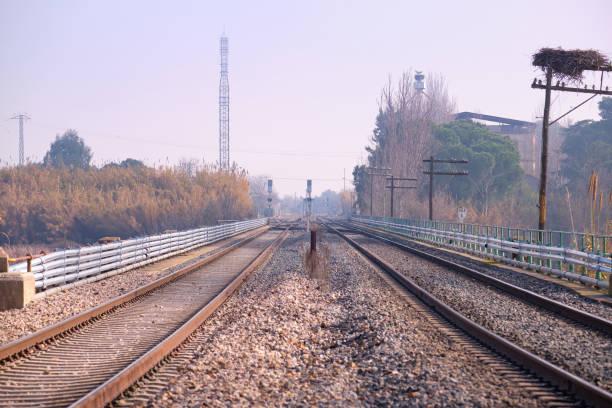 Vista de dos pistas paralelas sobre el ferrocarril cerca de una estación - foto de stock