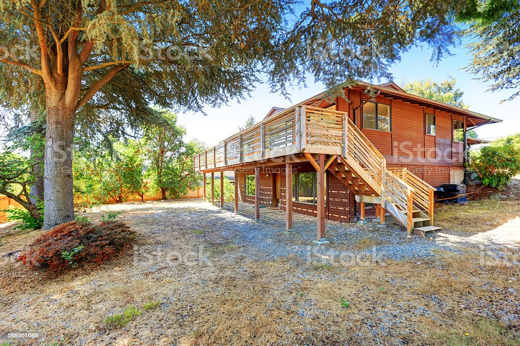 View of two story house with wooden trim and deck. stock photo