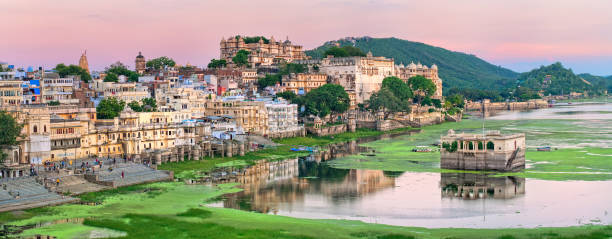 View of Udaipur, India, on sunset Maharajah palace and lake Pichola in the old town of Udaipur, India, on sunset lake pichola stock pictures, royalty-free photos & images