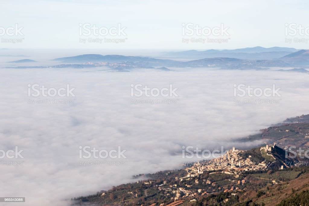 View of Umbria valley with Assisi town over a sea of fog royalty-free stock photo