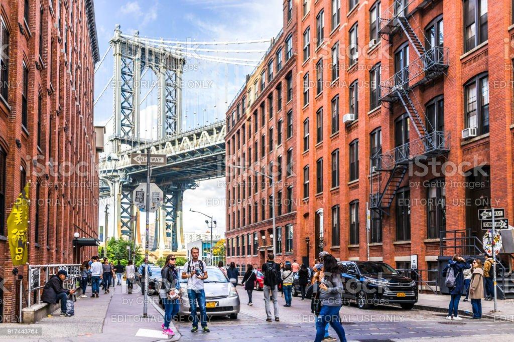 Vista sob a ponte de Manhattan em Dumbo fora exterior ao ar livre em NYC New York City, edifício de tijolo, céu azul, multidão ocupado de pessoas caminhando, loja japonesa - foto de acervo