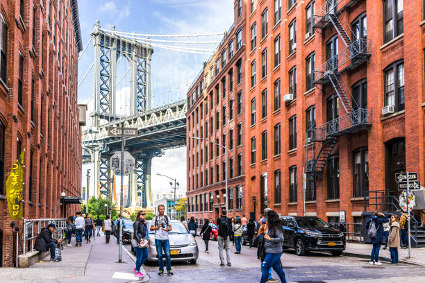 view of under manhattan bridge in dumbo outside exterior outdoors in nyc new york city, brick building, blue sky, people busy crowd walking, japanese store - lower east side manhattan stock pictures, royalty-free photos & images