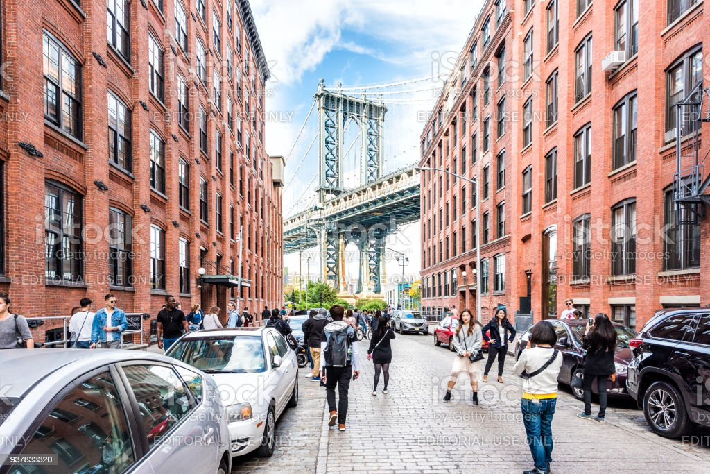 View of under Manhattan Bridge in Dumbo outside exterior outdoors in NYC New York City, brick building, blue sky, people busy crowd walking stock photo