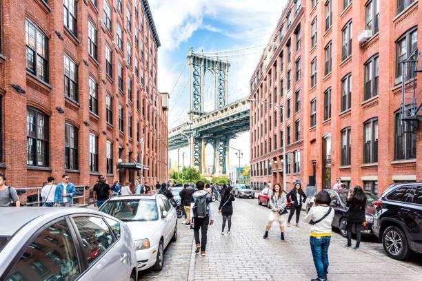 Vista sob a ponte de Manhattan em Dumbo fora exterior ao ar livre em NYC New York City, edifício de tijolo, céu azul, multidão ocupado de pessoas andando - foto de acervo