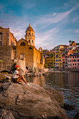 View of Vernazza one of Cinque Terre in the province of La Spezia, Italy, happy young couple picnic in the mountain with a look over the ocean Italy