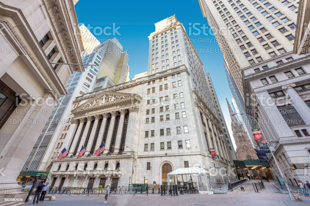 A view of Wall Street and New York Stock Exchange on a sunny day. stock photo