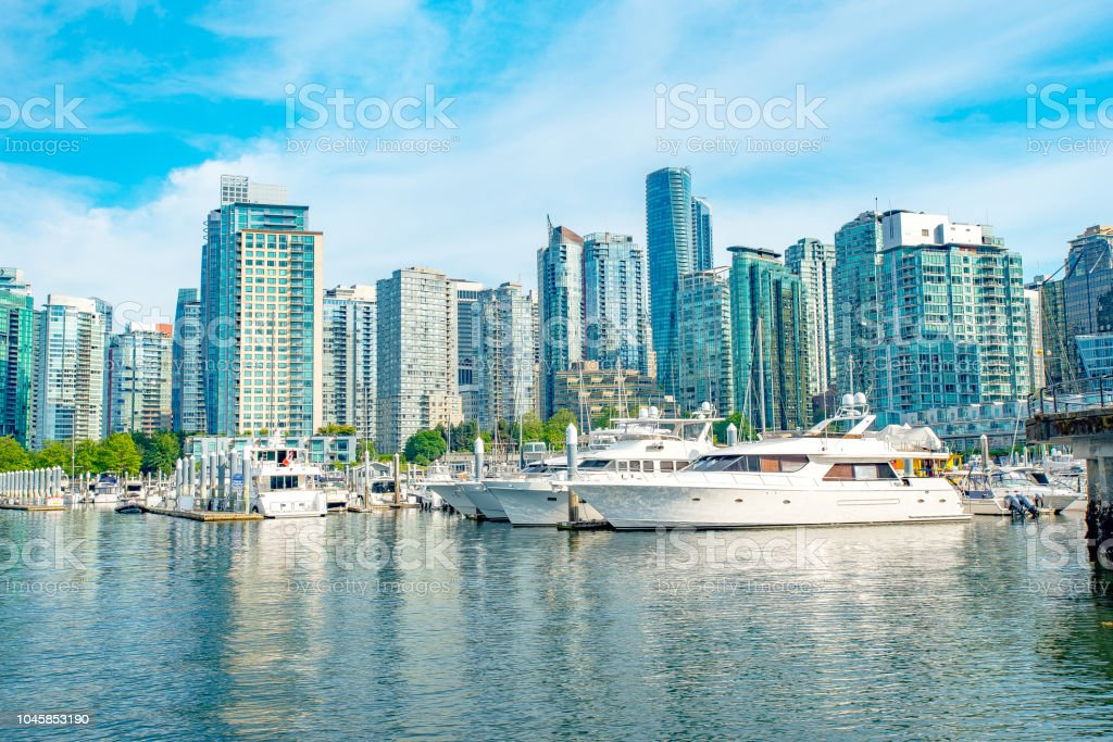 View of west vancouver marina with apartment and business buildings grouped around luxury yachts moored in marina stock photo