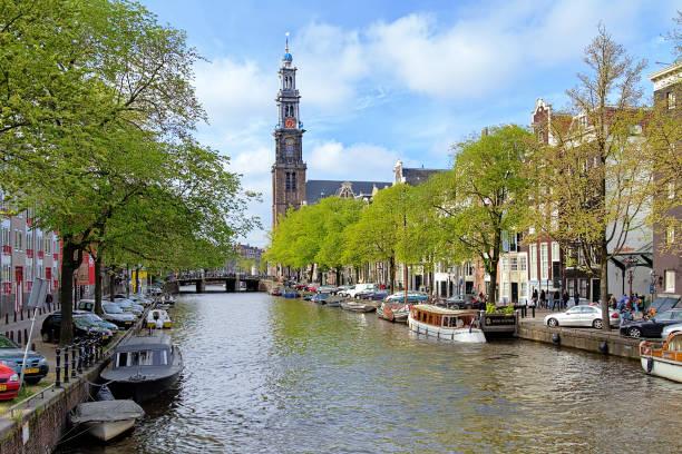 mening van de westerkerk prinsengracht kanaal in amsterdam, nederland - westerkerk stockfoto's en -beelden