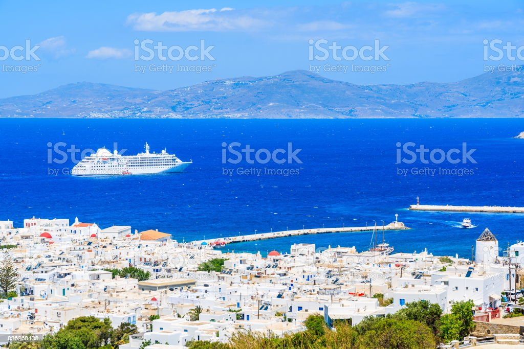 View of white houses of Mykonos town with cruise ship on sea in distance, Mykonos island, Greece stock photo