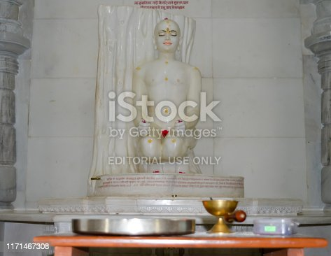 Parasnath, Giridih, Jharkhand, India May 2018  Close up View of White Marble Statue of a sitting Naked Jain Tirthankar Meditating on a Yoga Mudra. Digambara monks do not wear any clothes while Svetambara clad white.