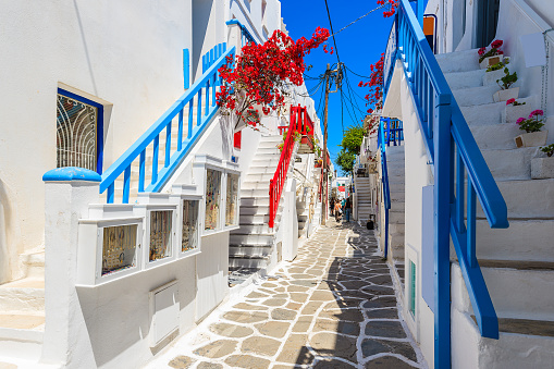 istock A view of whitewashed street with blue windows and flowers in beautiful Mykonos town, Cyclades islands, Greece 672664844