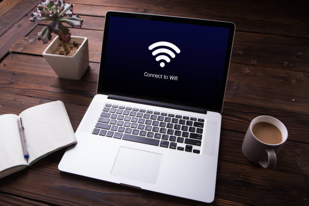 view of wi-fi connection on the laptop / computer screen with office equipment on wooden desk background - беспроводные технологии стоковые фото и изображения