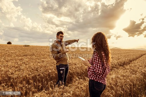 1094815168 istock photo View of woman and man at wheat field 1162924225