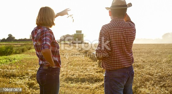 1094815168 istock photo View of woman and man looking at working combine-harvester 1094813618