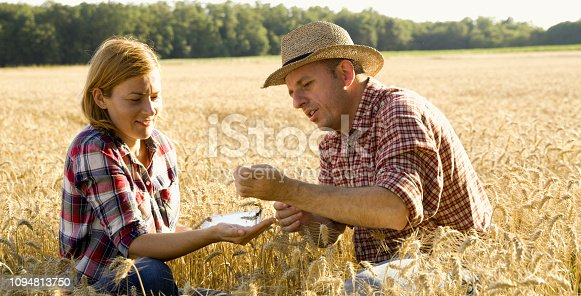 1094815168 istock photo View of woman and man sitting on field 1094813750