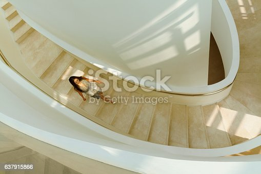istock View of woman descending staircase in modern building 637915866