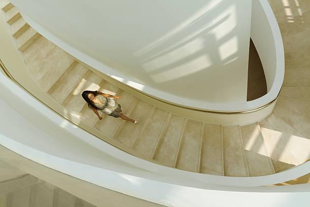 view of woman descending staircase in modern building - bogen bauen stock-fotos und bilder