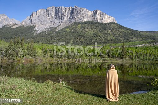 Wrapped in a blanket, she looks up to mountain across the lake