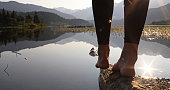 istock View of woman's feet as she walks, balancing on rock 1142967911