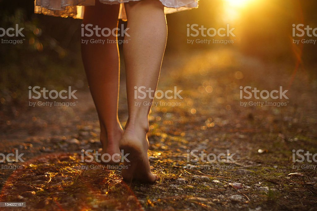 View of young woman's legs walking on dirt path stock photo