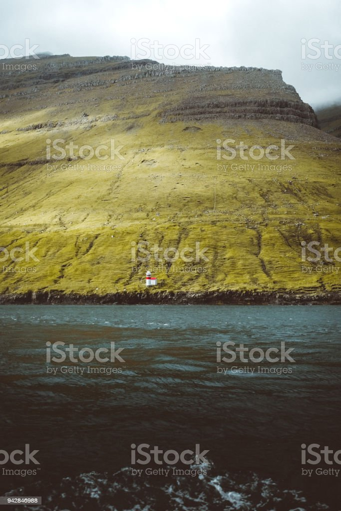 View On Abandoned Lighthouse From The Sea On Faroe Islands