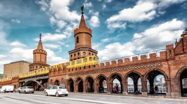 blick auf berlin oberbaumbrücke mit gelben u-bahn straßenbahn und autos auf der straße - oberbaumbrücke stock-fotos und bilder