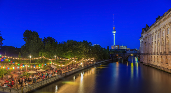 View on Berlin television tower and open air beer garden at shore of river Spree during evening twillight