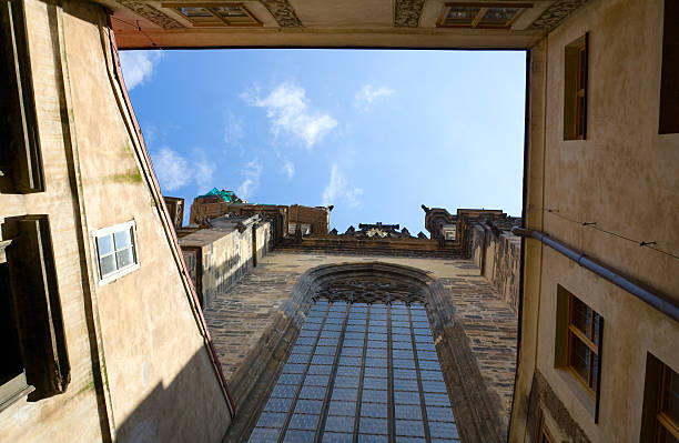 View on blue cloudy sky from church patio in Prague View on blue cloudy sky from inner encloused court of stone catholic gothic church of Virgin Mary Before Tyn with round-headed glass window in Prague Czech Republic tyn church stock pictures, royalty-free photos & images