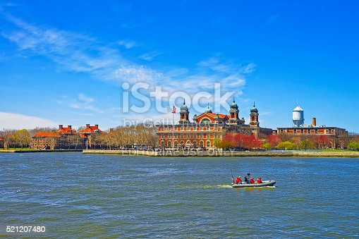New York City, USA - April 25, 2015: View on a boat and Ellis Island, USA, in Upper New York Bay. Tourists nearby