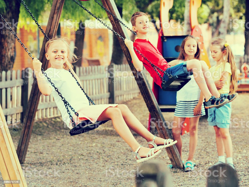 View on children swinging together on children's playground royalty-free stock photo