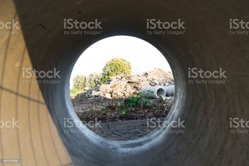 View On Construction Site Through Concrete Pipe Stock Photo