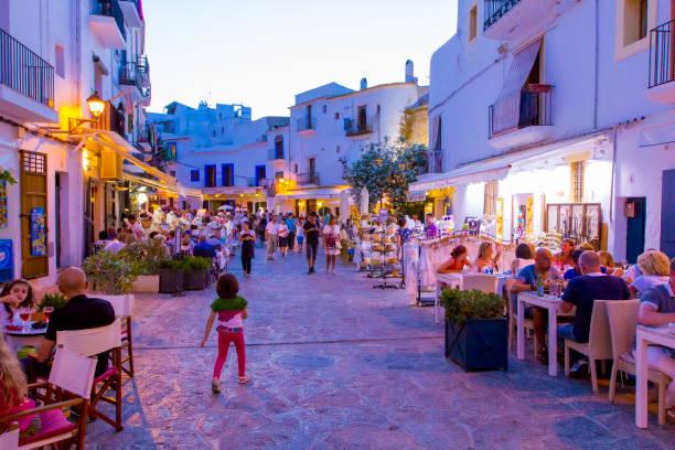 visa på fullsatt street med kafé, barer och restauranger i gamla stan dalt vila, på sommaren i kväll belysning, ibiza, spanien - walking home sunset street bildbanksfoton och bilder